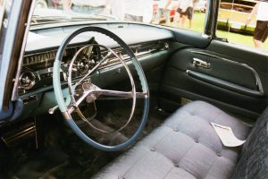 Interior photo of dash and stylish button and brocaded seat upholstery.